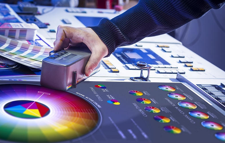 a hand working on finding the right color for an offset printing project